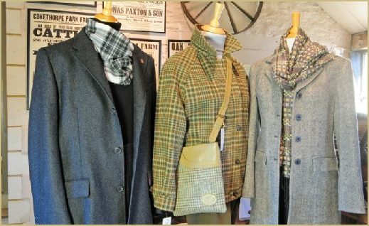 Three splendid woollen coats standing in the entrance lobby at Cotswold Woollen Weavers